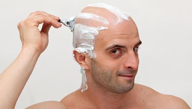 Мужчина бреет голову